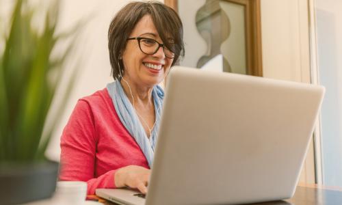 """alt=""""mulher mais velha no computador vendo ofertas de portabilidade"""""""
