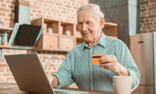 """alt=""""idoso com cartão consignado na mão olhando o computador"""""""